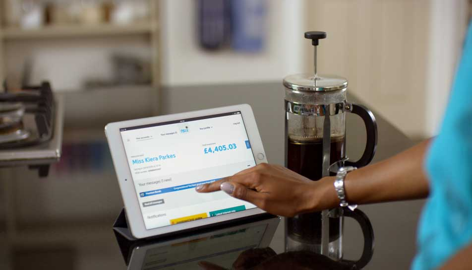 mum using NSANDI transactional site on a tablet next to a cafetiere on kitchen counter
